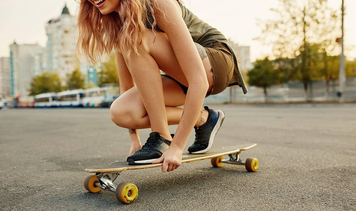best longboard brands girl riding longboard on street on a sunny day